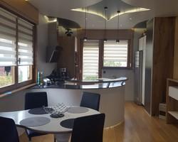 Menuiserie MENICA Buding - cuisine au design arrondi. Meubles en laqué blanc et chêne craquelé, plan de travail et table en résine de pierre (Corian). Emplacement après